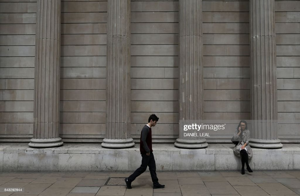 A womn talks on a mobile phone as a man walks past the Bank of England in the City of London on June 27, 2016. Britain should only trigger Article 50 to leave the EU when it has a 'clear view' of how its future in the bloc looks, finance minister George Osborne said Monday following last week's shock referendum. London stocks extended their losses in early afternoon Monday, led by banking, airline and property shares, following Britain's vote to leave the EU. / AFP / Daniel Leal-Olivas