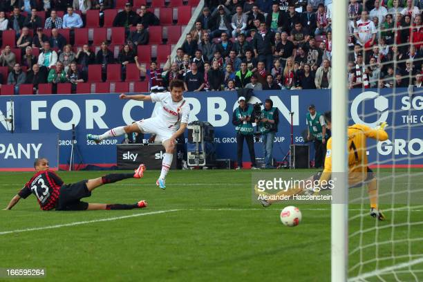 Won Dong Ji of Augsburg scores the second team goal against Oka Nikolov keeper of Frankfurt and his team mate Oliveira AndersonDe during the...