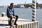 A depressed man sitting down outside on the dock with the ocean behind him, wearing jeans and a jeansshirt with sunglasses. Sunny summer day.