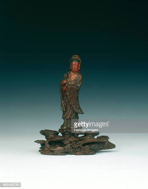 Wood and lacquer figure of Guanyin China 16441700 Early Qing dynasty carving of Guanyin holding a baby in her arms standing on top of a broad rock...
