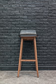 Wood and leather bar chair on black brick wall background, interior concept front view