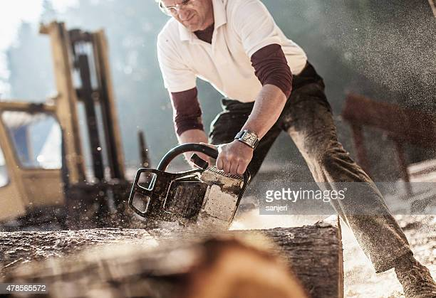 Wood artist working processing timber with chainsaw