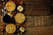Wood background with apple pies, tea and nuts. tonung. selective focus