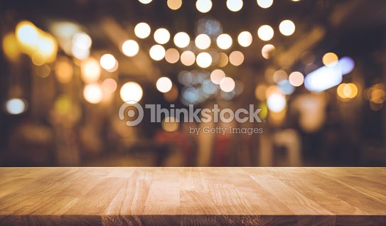 Wood bar table with blur lighting in night street cafe : Stock Photo