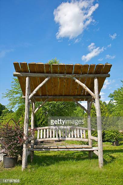 wood bench under canopy and blue skies.