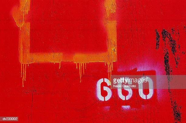 Wood board painted bright red with yellow square dripping paint and white numbers