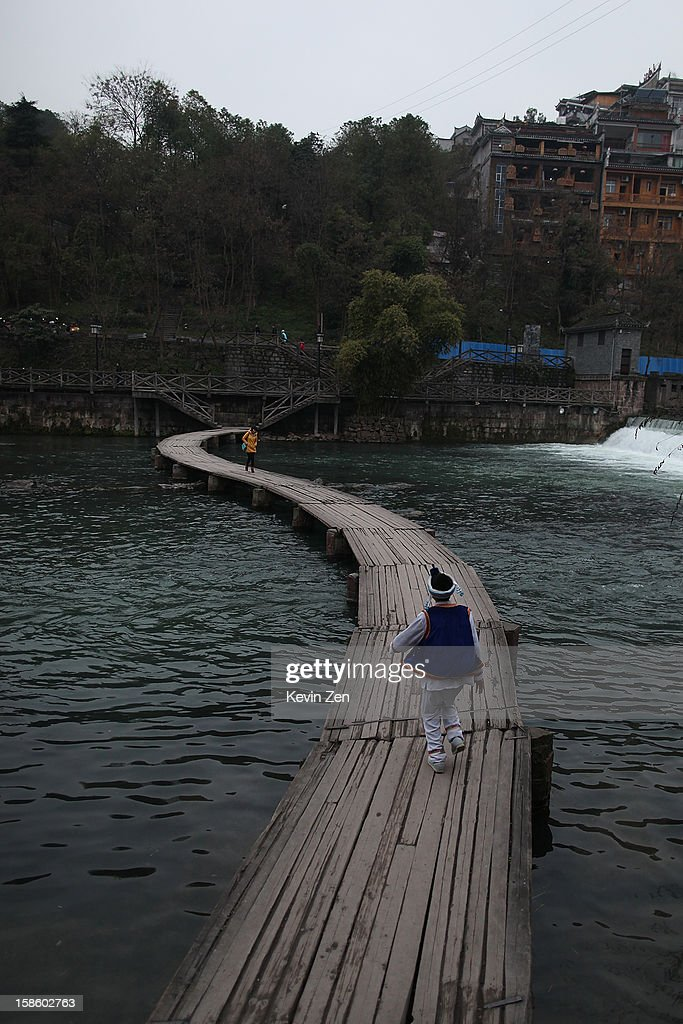 A wood bridge is on Tuojiang River in the old town on December 18, 2012 in Fenghuang, China. Fenghuang Town was built by Emperor Kangxi in 1704 and after 300 years, the city's ancient appearance has been well preserved. Hunan is located in southwest Hunan Provience of China with a population of 370,000 within a total area of 1700 square kilometers.