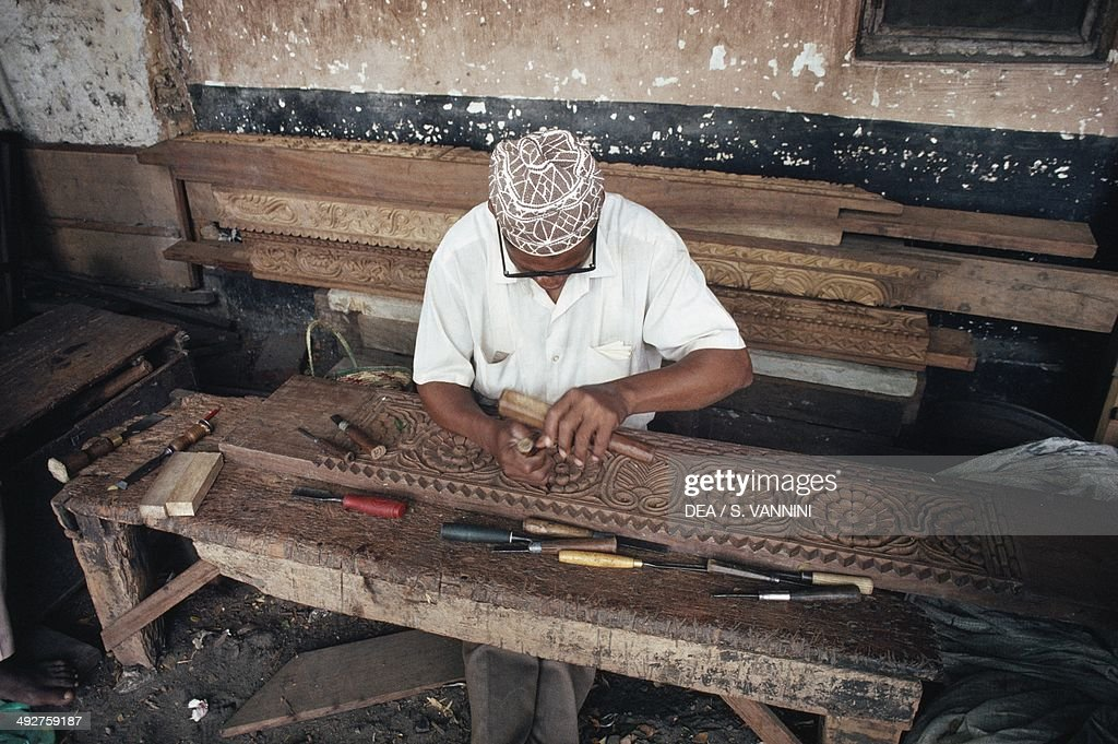 Wood carver working on a frame, Zanzibar, Tanzania.