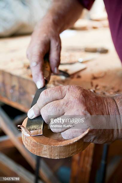 Wood carvers hands with chisel at work, close up.
