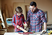 Father and son processing wooden plank in workshop