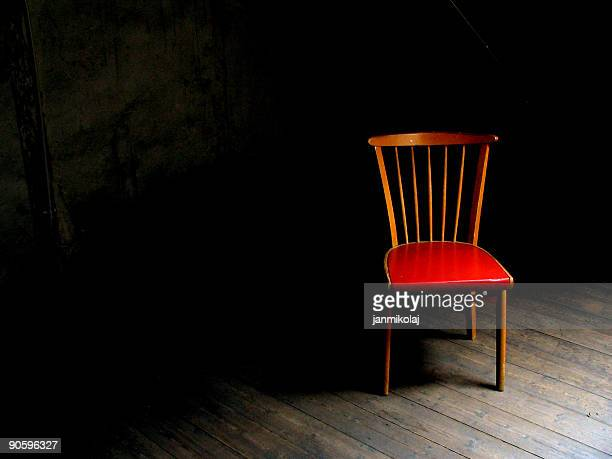 Wood chair with red seat in dark room with wood floor