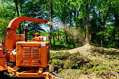 Landscapers using wood Chipper in Action captures a wood chipper or mulcher shooting chips over a fence.