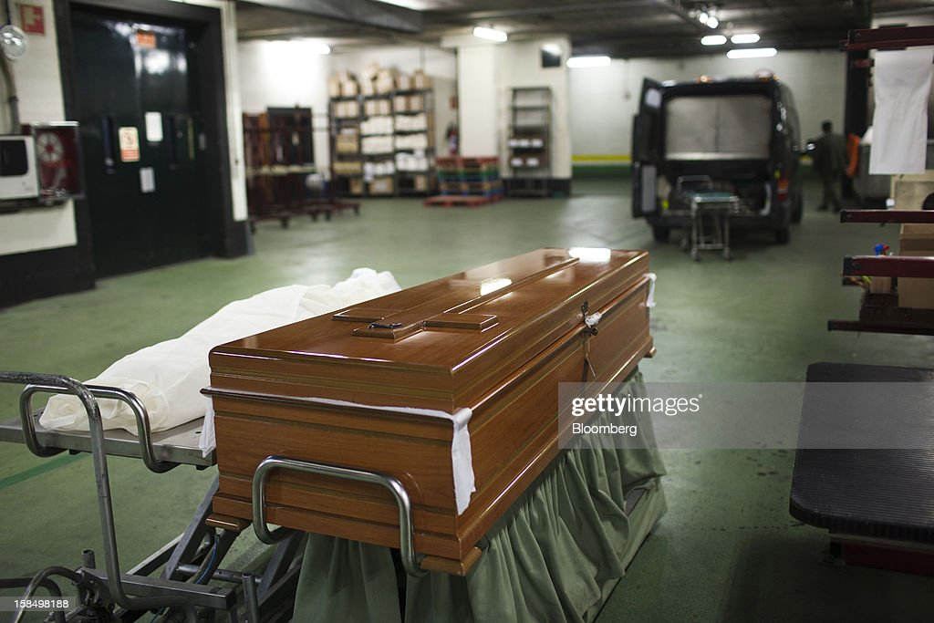 A wood coffin stands ready for use in the warehouse of the Empresa Mixta de Servicios Funerarios de Madrid SA funeral parlour in Madrid, Spain, on Monday, Dec. 17, 2012. Spain, responding to street protests and reports of suicides linked to foreclosures, introduced rules to help protect families from eviction, increasing the risk of creditor losses and weakening an already fragile banking system. Photographer: Angel Navarrete/Bloomberg via Getty Images