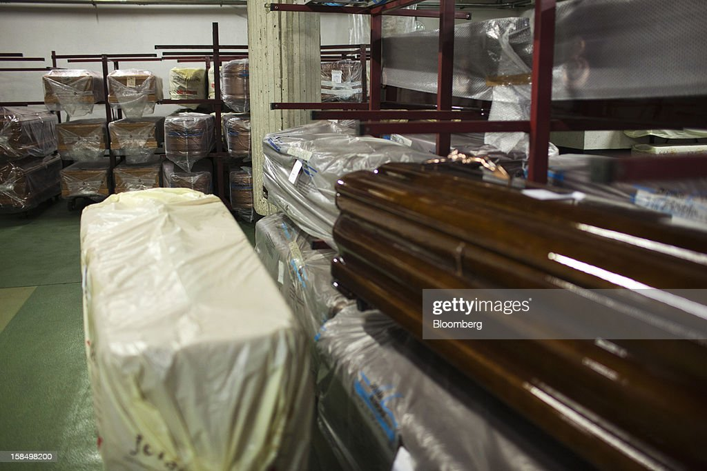 Wood coffins sit on racks inside the storage warehouse of the Empresa Mixta de Servicios Funerarios de Madrid SA funeral parlour in Madrid, Spain, on Monday, Dec. 17, 2012. Spain, responding to street protests and reports of suicides linked to foreclosures, introduced rules to help protect families from eviction, increasing the risk of creditor losses and weakening an already fragile banking system. Photographer: Angel Navarrete/Bloomberg via Getty Images