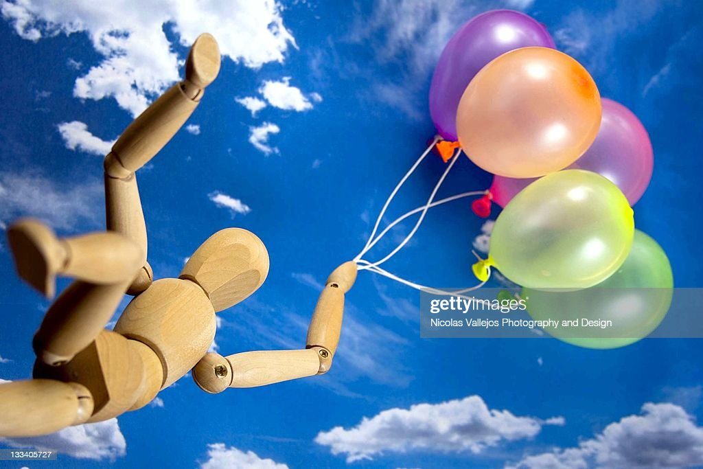 Wood figure carried away by party balloons : Stock Photo