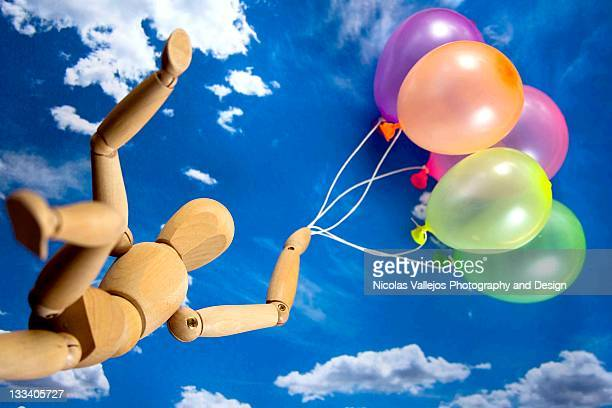 Wood figure carried away by party balloons