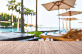 Wood floor with blur summer background tropical resort hotel with blue swimming pool and palm tree