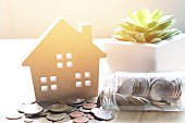 Business, finance, savings, property ladder, mortgage or loan concept : Wood house model and coins scattered from glass jar on wooden background