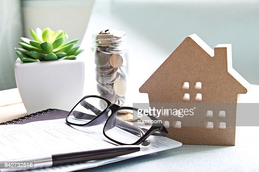 Wood house model, coins, eyeglasses and saving account book or financial statement on office desk table : Stock Photo