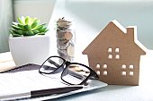 Business, finance, saving money, banking, property loan or mortgage concept :  Wood house model, coins, eyeglasses and saving account book or financial statement on office desk table