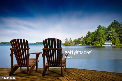 Wood Muskoka chairs on a lake deck : Stock Photo