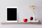 Wood shelf with tablet and coffee. Blank screen for products or graphic montage.