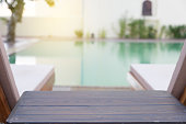 wood table and pool chair for resting and relaxing at poolside of swimming pool