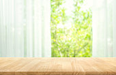 Empty of wood table top on blur of curtain with window view green from tree garden background.For montage product display or design key visual layout