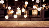 Wood table top on blurred of counter cafe shop with light bulb background.For montage product display or design key visual layout.Wood table top on blurred of counter cafe shop with light bulb backgro
