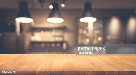 Wood table on blurred of counter cafe with light bulb : Stock Photo