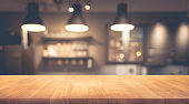 Wood table top on blurred of counte cafe shop with light bulb background.For montage product display or design key visual layout.