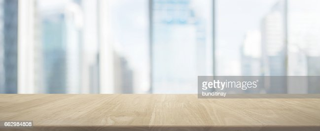 Wood table top and blur glass window wall building banner background : Stock Photo