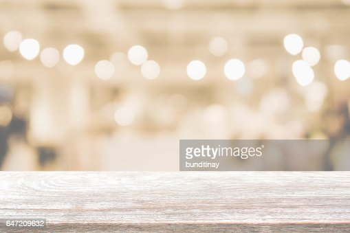 Wood table top and blurred restaurant interior background with vintage filter. : Stock Photo