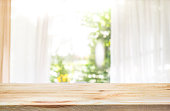 Empty of wood table top on blur of curtain window in home with green garden view.For product display summer concept