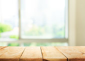 Empty wood table top on blur abstract green garden from window view in the morning.For montage product display or design key visual layoutEmpty wood table top on blur abstract green garden from window
