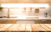 Wood table top on blur kitchen room interior background .For montage product display or design key visual layout.