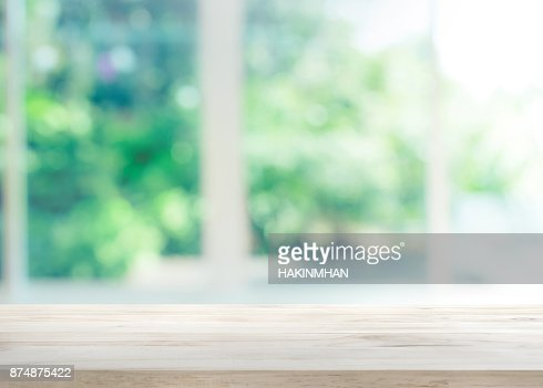 Wood table top on blur of window with garden flower : Stock Photo