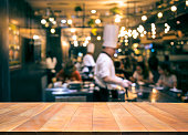 Wood table top with blur chef cooking in bar restaurant background.For create product display or design key visual layout