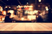 Wood table top with blur light bokeh in night cafe background .Lifestyle and celebration concepts