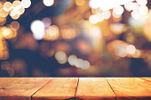 Empty of wood  table top with  blurred light gold bokeh abstract background.For montage product display or design key visual layoutEmpty of wood  table top with  blurred light gold bokeh abstract back