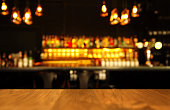 wood table with blur light of lamp and bar with bottle abstract bacgournd