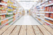 Wood table with Empty Supermarket aisle shelves abstract blur defocused business background, product display template