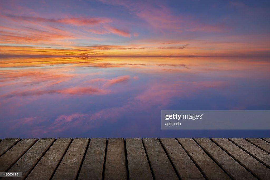 wood terrace and the reflection of sunset on sea water : Stock Photo