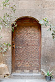 Wooden aged vaulted engraved door and stone wall, Medieval Cairo, Egypt