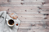 Wooden background with cup of coffee and ginger cookies on the linen napkin