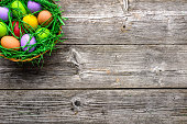Wooden background with easter eggs in the basket, top view