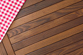 Wooden background with red and white checkered tablecloth. Top view, blank space