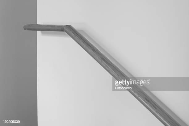 Wooden banister along wall, black and white