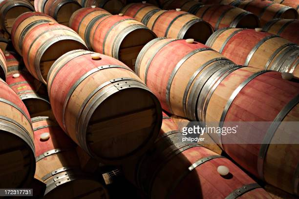 Wooden barrels stacked atop one another in a dimly lit area