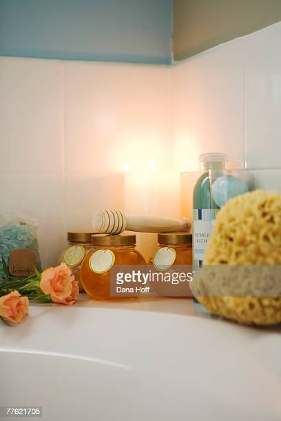 A wooden bath caddy and candles on the edge of a bathtub